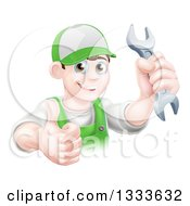 Clipart Of A Happy Young Brunette Caucasian Mechanic Man In Green Wearing A Baseball Cap Holding A Wrench And Thumb Up Royalty Free Vector Illustration