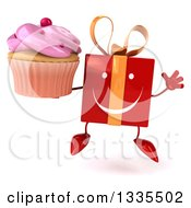 Clipart Of A 3d Happy Red Gift Character Jumping And Holding A Pink Frosted Cupcake Royalty Free Illustration by Julos