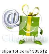 Clipart Of A 3d Happy Green Gift Character Holding An Email Arobase At Symbol Royalty Free Illustration
