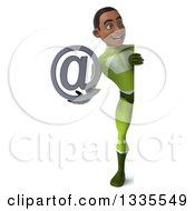 Clipart Of A 3d Full Length Young Black Male Super Hero In A Green Suit Holding An Email Arobase At Symbol And Looking Around A Sign Royalty Free Illustration