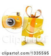 Clipart Of A 3d Happy Yellow Gift Character Holding And Pointing To A Camera Royalty Free Illustration by Julos