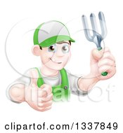 Clipart Of A Happy Young Brunette White Male Gardener In Green Holding Up A Garden Fork And Thumb Royalty Free Vector Illustration