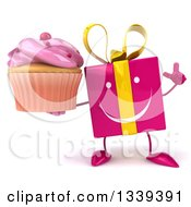 Clipart Of A 3d Happy Pink Gift Character Holding Up A Finger And A Frosted Cupcake Royalty Free Illustration by Julos