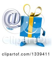 Clipart Of A 3d Happy Blue Gift Character Holding An Email Arobase At Symbol Royalty Free Illustration by Julos