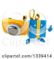 Clipart Of A 3d Happy Blue Gift Character Holding Up A Thumb Up And A Camera Royalty Free Illustration by Julos