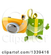 Clipart Of A 3d Happy Green Gift Character Holding Up A Thumb Up And A Camera Royalty Free Illustration