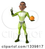Clipart Of A 3d Young Black Male Super Hero In A Green Suit Holding Up A Finger And A Navel Orange Royalty Free Illustration