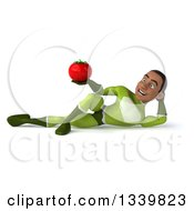 Clipart Of A 3d Young Black Male Super Hero In A Green Suit Holding A Tomato And Resting On His Side Royalty Free Illustration