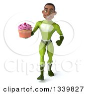 Clipart Of A 3d Young Black Male Super Hero In A Green Suit Holding A Pink Frosted Cupcake And Walking Royalty Free Illustration