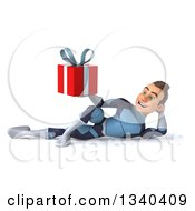 Clipart Of A 3d Young Brunette White Male Super Hero In A Dark Blue Suit Resting On His Side And Holding A Gift Royalty Free Illustration
