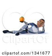 Clipart Of A 3d Young Black Male Super Hero Dark Blue Suit Holding A Navel Orange And Resting On His Side Royalty Free Illustration