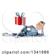 Clipart Of A 3d Young Brunette White Male Super Hero In A Dark Blue Suit Resting On His Side And Holding A Red Gift Royalty Free Illustration