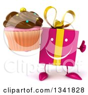 Clipart Of A 3d Happy Pink Gift Character Holdinga Chocolate Frosted Cupcake And Giving A Thumb Up Royalty Free Illustration