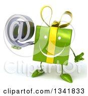 Clipart Of A 3d Happy Green Gift Character Shrugging And Holding An Email Arobase At Symbol Royalty Free Illustration