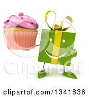 Clipart Of A 3d Happy Green Gift Character Holding And Pointing To A Pink Frosted Cupcake Royalty Free Illustration