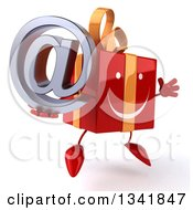 Clipart Of A 3d Happy Red Gift Character Holding An Email Arobase At Symbol Facing Slightly Right And Jumping Royalty Free Illustration by Julos
