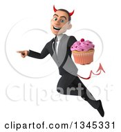 Clipart Of A 3d Young White Devil Businessman Holding A Pink Frosted Cupcake Flying And Pointing To The Left Royalty Free Illustration