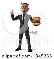Clipart Of A 3d Young Black Devil Businessman Holding Up A Finger And A Double Cheeseburger Royalty Free Illustration