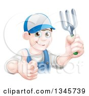 Clipart Of A Happy Young Brunette White Male Gardener In Blue Holding Up A Garden Fork And Thumb Royalty Free Vector Illustration