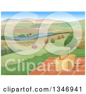 Picnic Basket And Blanket On A Hill With A View Of A Lake And Farm Lands