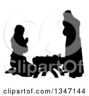 Clipart Of A Black And White Silhouetted Mary And Joseph Praying Over Baby Jesus Royalty Free Vector Illustration by AtStockIllustration