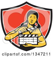 Clipart Of A Retro Female Asian Film Crew Worker Holding A Clapper In A Black White And Red Shield Royalty Free Vector Illustration
