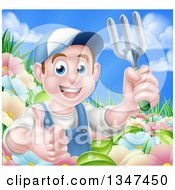 Clipart Of A Happy Young Brunette White Male Gardener In Blue Holding Up A Garden Fork And Thumb In A Flower Garden Royalty Free Vector Illustration