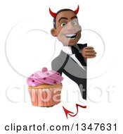 Clipart Of A 3d Young Black Devil Businessman Holding A Cupcake Around A Sign Royalty Free Illustration