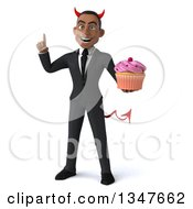 Clipart Of A 3d Young Black Devil Businessman Holding Up A Finger And A Cupcake Royalty Free Illustration