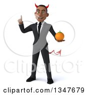 Clipart Of A 3d Young Black Devil Businessman Holding Up A Finger And A Navel Orange Royalty Free Illustration