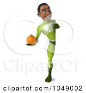 Clipart Of A 3d Full Length Young Black Male Super Hero In A Green Suit Holding A Navel Orange Around A Sign Royalty Free Illustration by Julos
