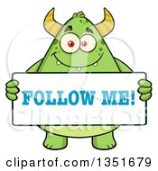 Clipart Of A Cartoon Chubby Green Horned Monster Holding A Follow Me Sign Royalty Free Vector Illustration