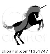 Clipart Of A Black Silhouetted Rearing Rampant Unicorn In Profile Facing Right Royalty Free Vector Illustration by AtStockIllustration