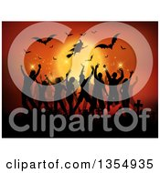 Silhouetted Flying Halloween Witch And Bats Against A Full Moon Over People Dancing In A Cemetery