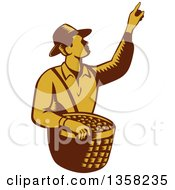 Clipart Of A Retro Woodcut Brown And Yellow Male Farm Fruit Picker Worker Pointing And Holding A Basket Royalty Free Vector Illustration