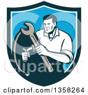 Clipart Of A Retro Male Mechanic Holding A Wrench And Shield Inside A Blue And White Shield Royalty Free Vector Illustration