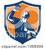 Clipart Of A Retro Male Athlete Doing A Fist Pump In A Blue White And Orange Shield Royalty Free Vector Illustration