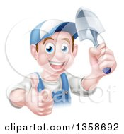 Clipart Of A Happy Young Brunette White Male Gardener In Blue Giving A Thumb Up And Holding A Shovel Royalty Free Vector Illustration