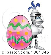 Clipart Of A Lancer School Mascot Posing By An Easter Egg Royalty Free Vector Illustration by Toons4Biz