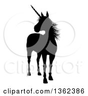 Clipart Of A Black Silhouetted Mythical Unicorn Standing And Looking To The Left Royalty Free Vector Illustration