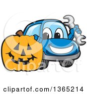 Happy Blue Car Mascot Holding A Wrench By A Halloween Jackolantern Pumpkin