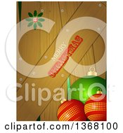 Clipart Of A Merry Christmas Greeting On Wood Panels With Holly And 3d Baubles Royalty Free Vector Illustration