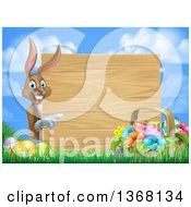 Clipart Of A Brown Easter Bunny Rabbit With Eggs And A Basket Pointing Around A Blank Wood Sign Against Sky Royalty Free Vector Illustration