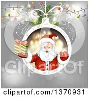 Christmas Santa Claus Holding Up A Gift In A Bauble Frame Over Gray With Lights