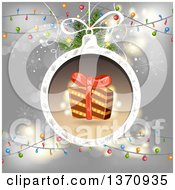 Clipart Of A Gift In A Christmas Bauble Frame Over Gray With Lights Royalty Free Vector Illustration