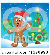 Happy Gingerbread Man Cookie Waving And Holding A Christmas Gift By A Tree