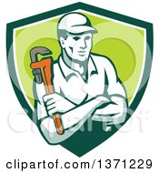 Clipart Of A Retro Male Plumber Holding A Monkey Wrench With Folded Arms In A Green And White Shield Royalty Free Vector Illustration
