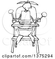 Black And White Baby Lamb Sitting In A High Chair And Wearing A Bib
