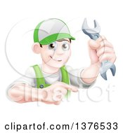 Clipart Of A Happy Young Brunette Caucasian Mechanic Man In Green Wearing A Baseball Cap Holding A Wrench And Pointing Royalty Free Vector Illustration
