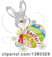 Clipart Of A Gray Bunny With A Decorated Happy Easter Egg Royalty Free Vector Illustration